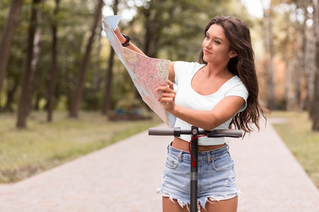 Front view of woman looking at map next to electric scooter