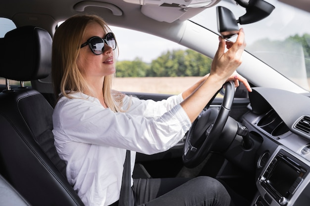 Front view of a woman looking at rearview mirror