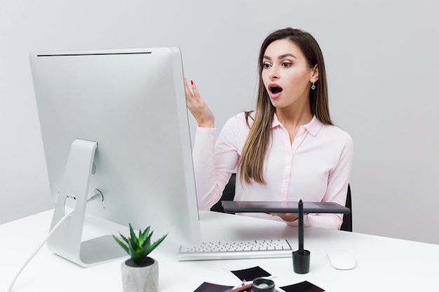 Front view of woman looking surprised at computer screen