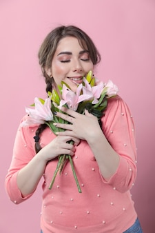 Front view of woman loving her bouquet of lilies
