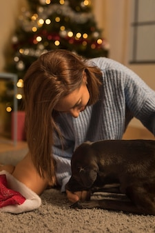 Front view of woman loving her dog on christmas