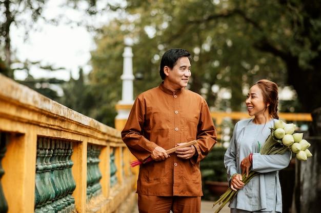 Vista frontale della donna e dell'uomo che tengono il mazzo di fiori al tempio e l'incenso