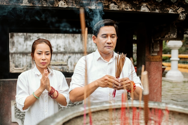 Front view of woman and man praying at the temple with burning incense