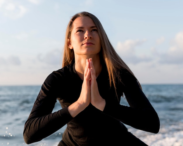 ビーチで瞑想する正面図の女性