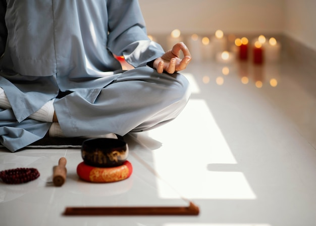 Front view of woman meditating with incense and candles