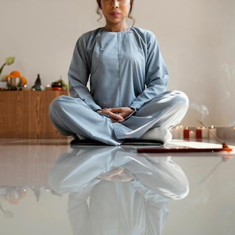 Front view of woman meditating with incense
