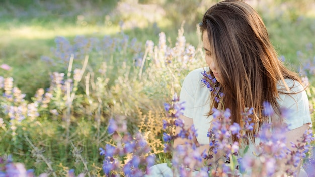 Front view of woman in nature admiring flowers