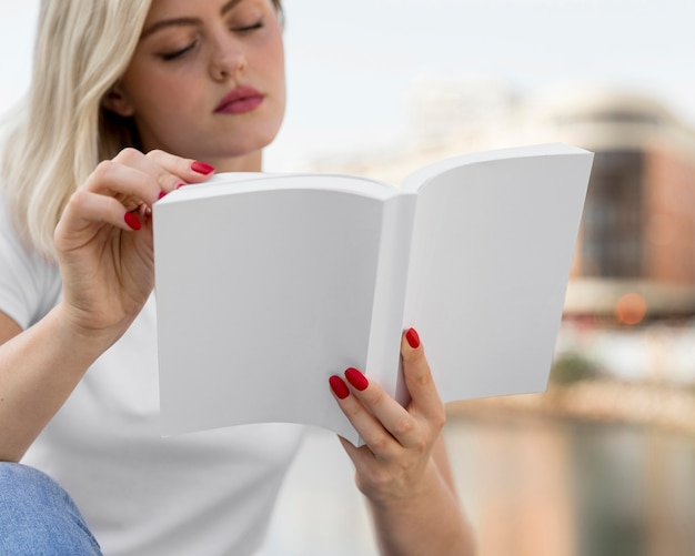 Front view of woman outdoors reading book