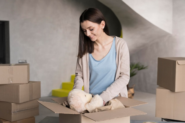 Front view of woman packing teddy bear in delivery box