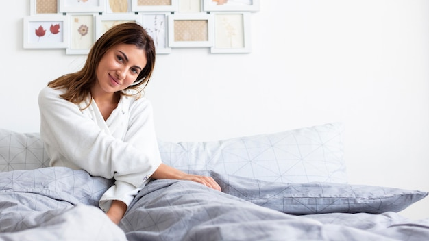 Front view of woman in pajamas relaxing in bed