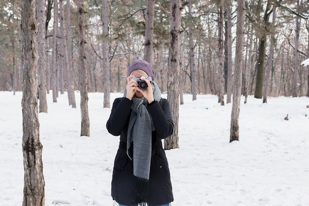 Front view of woman photographer with camera in winter