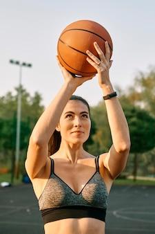 一人でバスケットボールをしている正面図の女性