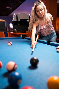 Front view woman playing billiard