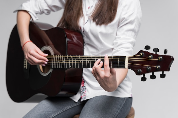 Front view woman playing chords on guitar