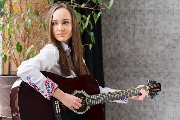 Женщина вид спереди играет аккорды на гитаре и смотрит в сторону