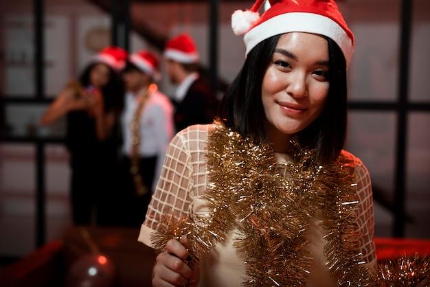 Donna di vista frontale che gioca con una ghirlanda alla festa di capodanno
