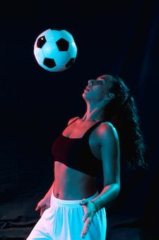 Front view woman playing with soccer ball