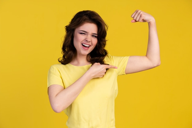 Front view of woman pointing to her bicep