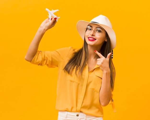 Front view of woman pointing at plane figurine that she's holding