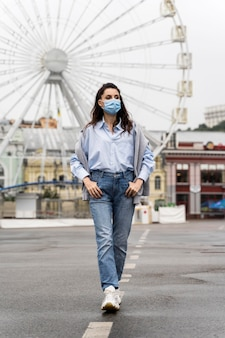 Front view woman posing in an amusement park while wearing a medical mask