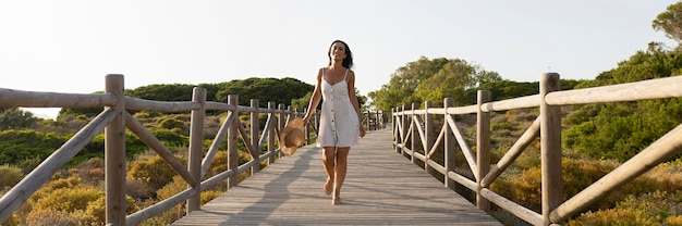 Vista frontale della donna che posa sul ponte in natura