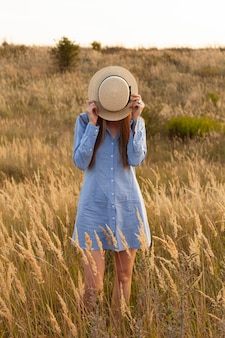 Front view of woman posing in the fields with hat