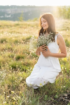 Front view of woman posing in grass with flowers