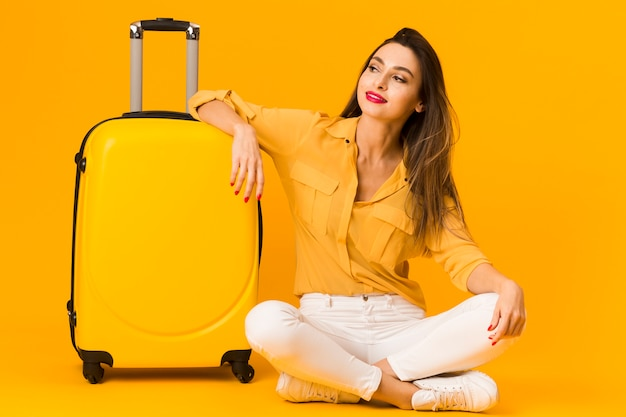 Front view of woman posing happily next to her luggage