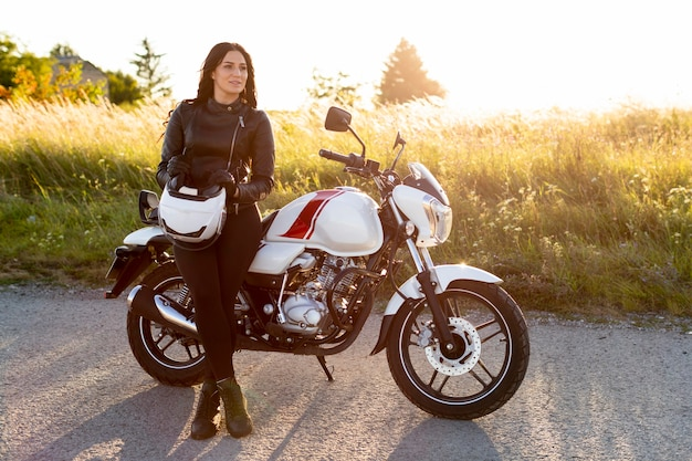 Front view of woman posing next to her motorcycle