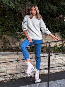 Front view of woman posing in jeans and roller skates behind handrail
