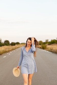 Front view of woman posing in the middle of the road with copy space