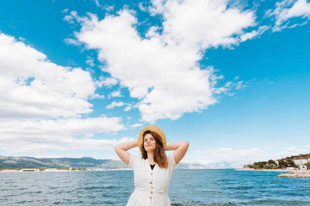 Front view of woman posing at the ocean with clouds in the sky