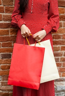Vista frontale della donna in posa all'esterno tenendo più borse della spesa
