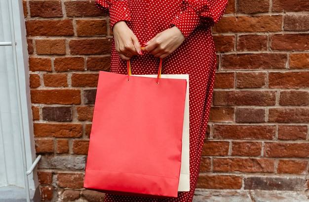 Vista frontale della donna che propone all'esterno con più borse della spesa
