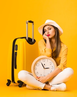 Front view of woman posing while holding clock next to luggage