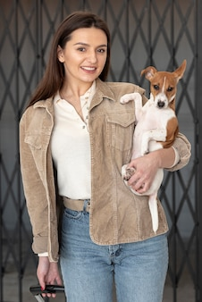 Front view of woman posing while holding her dog in arms