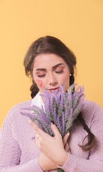 Front view of woman posing while smelling lavender