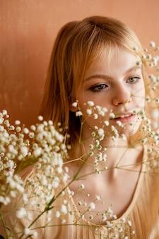 Vista frontale della donna in posa con fiori delicati