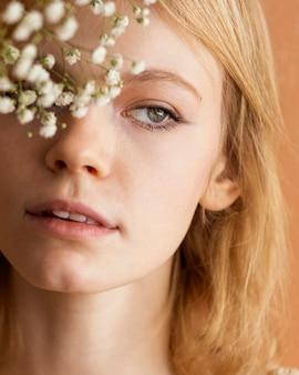 Vista frontale della donna in posa con i fiori