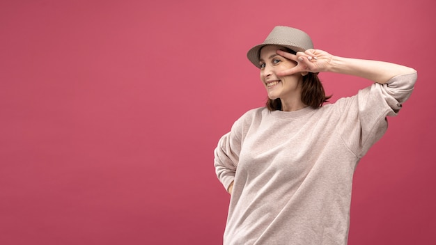 Front view of woman posing with hat and copy space