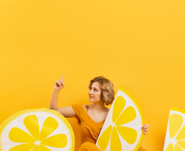Front view of woman posing with lemon slices decor and pointing up