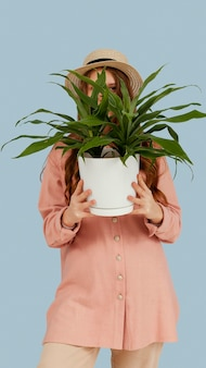 Front view of woman posing with pot of plant