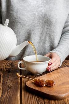 Vista frontale del concetto di versamento del tè della donna