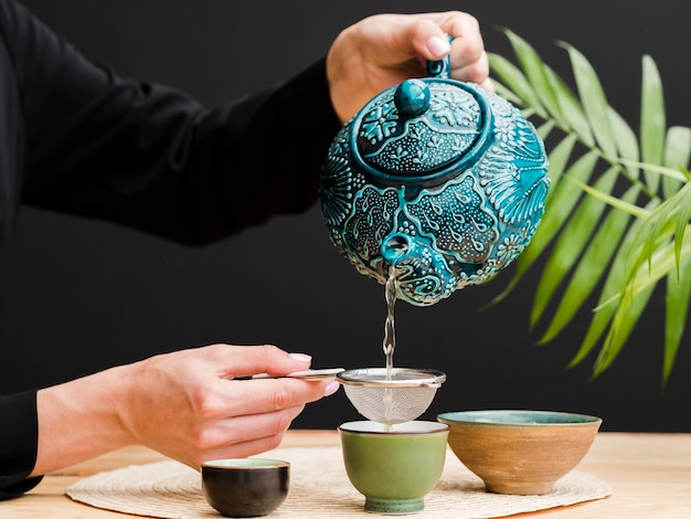 Front view woman pouring tea in teacup using strainer