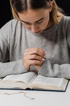 Vista frontale della donna che prega e legge dalla bibbia