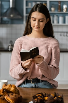 Vista frontale della donna che prega con la bibbia