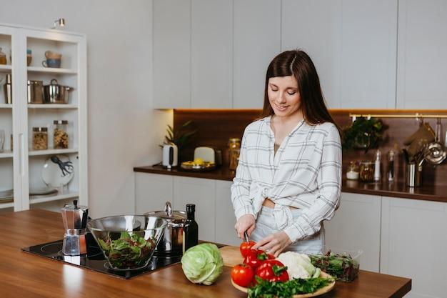 Vista frontale della donna che prepara il cibo in cucina