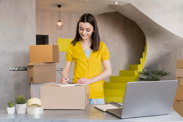 Front view of woman preparing orders in boxes to ship