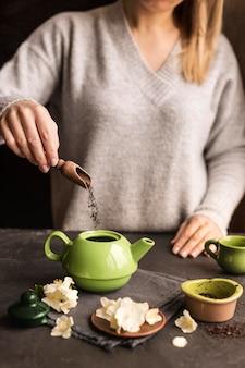 Vista frontale della donna che prepara concetto del tè