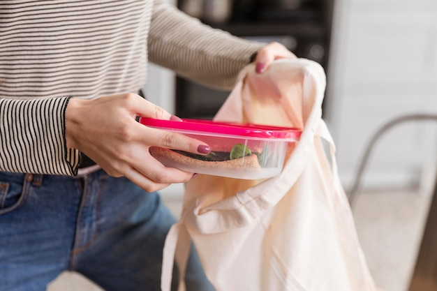 Front view woman puts lunch boxes in bag